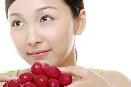 femme regarde en haut: Woman looking up while holding grapes.