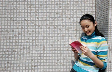 revision book: Girl leaning against the wall while reading book. LANG_EVOIMAGES