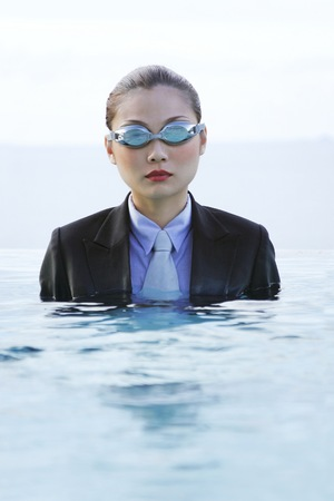 Businesswoman in goggles and suit sitting in the swimming pool.