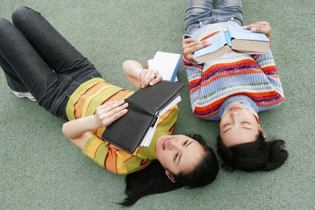 revision book: Two girls studying together.
