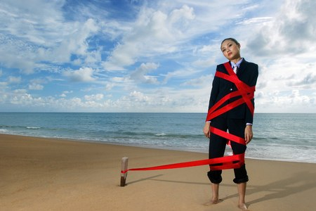 wrapped up: Businesswoman being tied up on the beach.