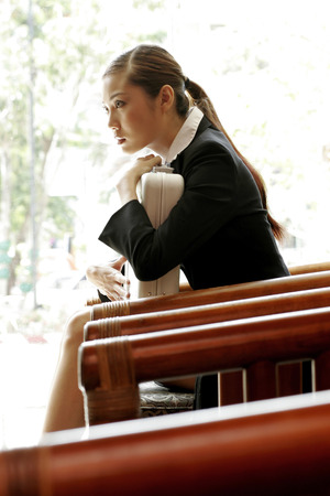 wasting away: Businesswoman hugging her briefcase.