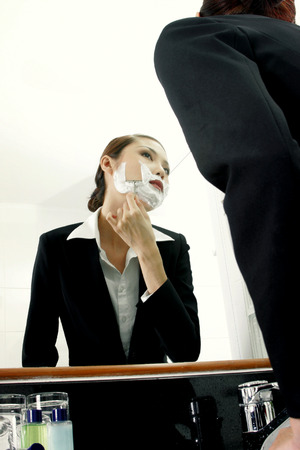 role reversal: Businesswoman shaving.