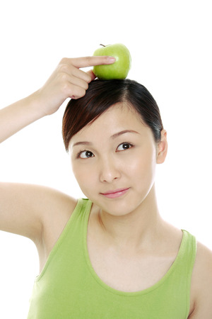 Woman placing a green apple on her head.