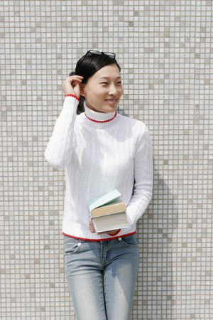 revision book: Girl leaning against the wall holding a stack of books. LANG_EVOIMAGES