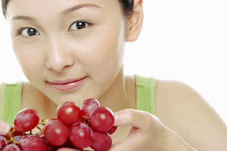 fair complexion: Woman posing with grapes.