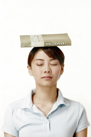 revision book: Woman closing her eyes while balancing a dictionary on her head