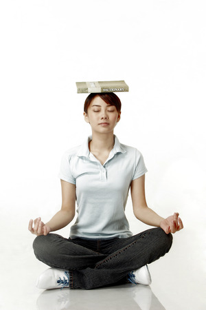revision book: Woman balancing a dictionary on her head while meditating