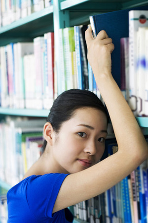 revision book: Young woman posing in the library
