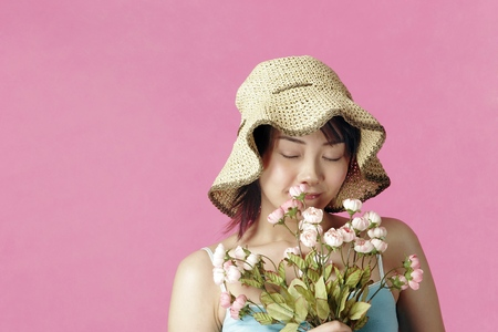 smelling: Woman with hat smelling flowers