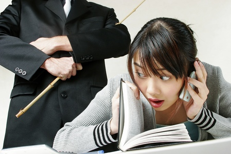 revision book: Woman talking on the phone with her teacher watching from her back