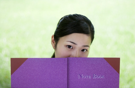 revision book: Young woman reading book in the park