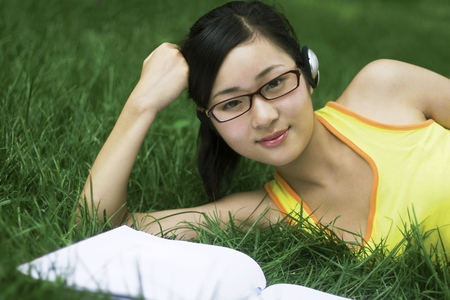 revision book: Young woman listening to music on the headphones while reading LANG_EVOIMAGES