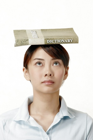 revision book: Woman looking up while balancing a dictionary on her head LANG_EVOIMAGES