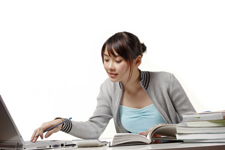 revision book: Woman using laptop and reading books LANG_EVOIMAGES
