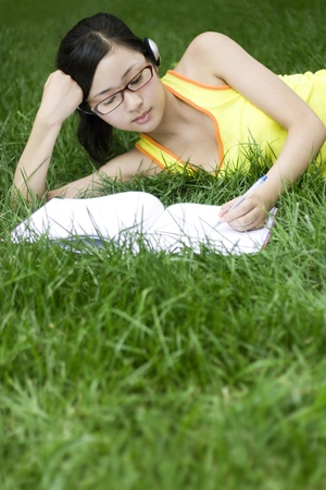 revision book: Young woman lying on the field reading book LANG_EVOIMAGES