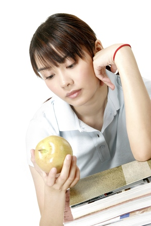revision book: Woman looking at an apple while resting on a stack of books LANG_EVOIMAGES