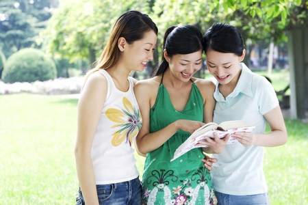 revision book: Three young women sharing a book