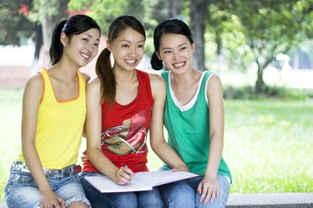revision book: Three beautiful young women in the park LANG_EVOIMAGES