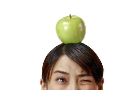 sensory perception: Woman winking her eye while balancing an apple on her head
