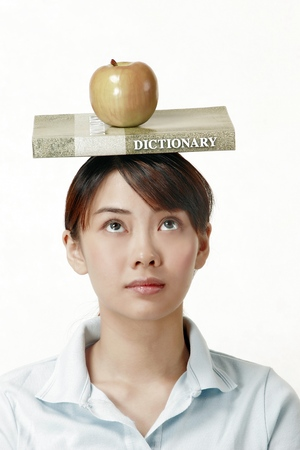 revision book: Woman looking up while balancing a dictionary and an apple on her head LANG_EVOIMAGES