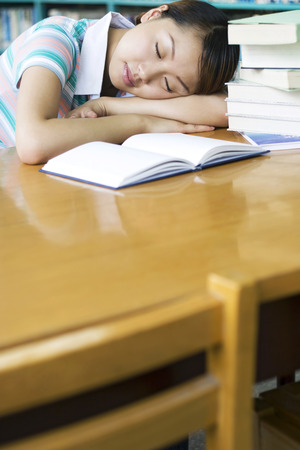 revision book: Young woman sleeping in the library