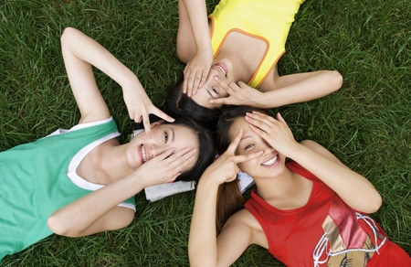 revision book: Three lovely young women lying on the field posing for the camera