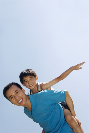 Father carrying son on his back Stock Photo