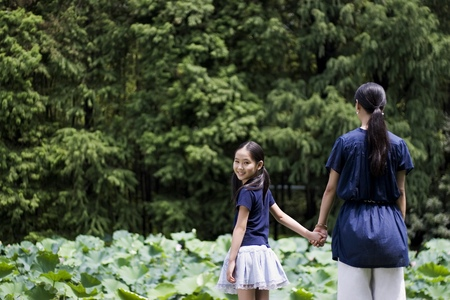 holding hands while walking: Mother and daughter holding hands while walking in the park LANG_EVOIMAGES