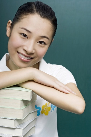 revision book: Young woman posing with a stack of books