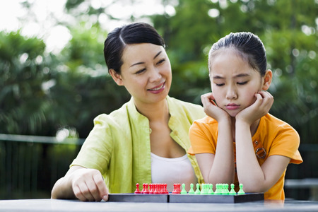 sulking: Mother watching daughter sulking while playing chinese checkers LANG_EVOIMAGES