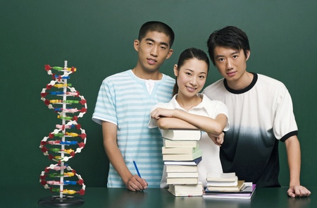 revision book: Young woman posing with her male course mates LANG_EVOIMAGES