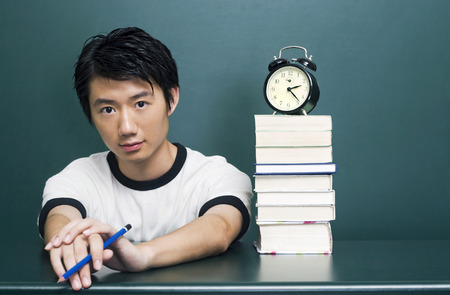 revision book: Young man sitting near a stack of books
