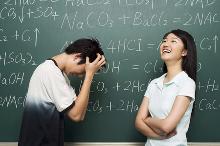 Young man scratching head while young woman laughing with confidence Stock Photo