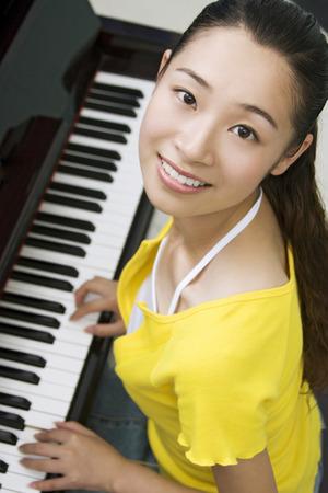 tocando el piano: Mujer joven que juega el piano LANG_EVOIMAGES