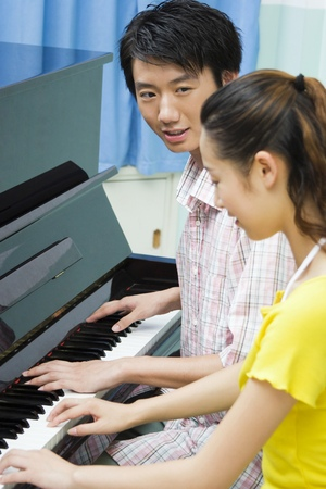 playing piano: Young couple playing piano together