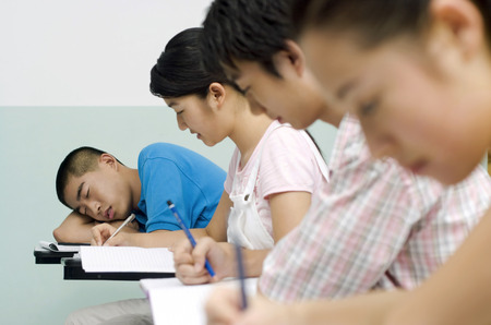 young man: Young man sleeping in the class
