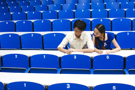 lecture theatre: Young woman copying her course mate's work
