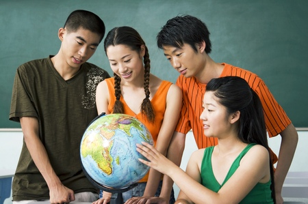 finding a mate: College students studying a globe