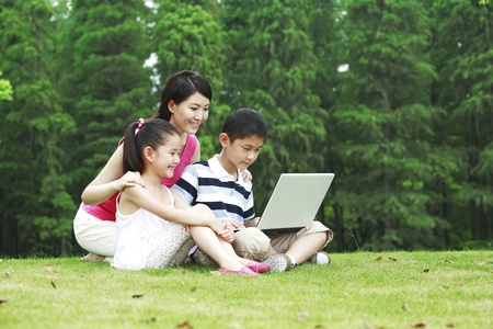 he   my sister: Mother and children using laptop in the park LANG_EVOIMAGES