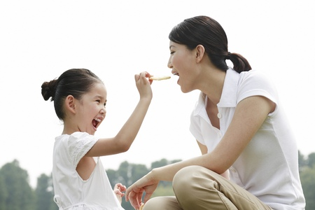 Girl feeding her mother with biscuit