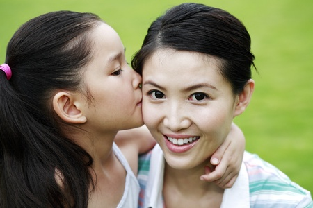 peck: Girl giving her mother a peck on the cheek