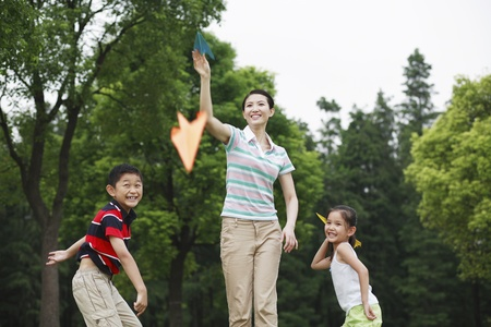he   my sister: Mother and children throwing paper planes in the park