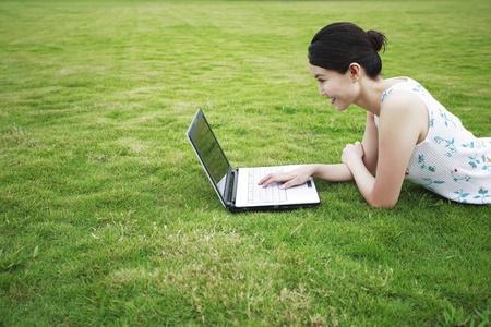 lying forward: Woman lying forward on the grass using laptop