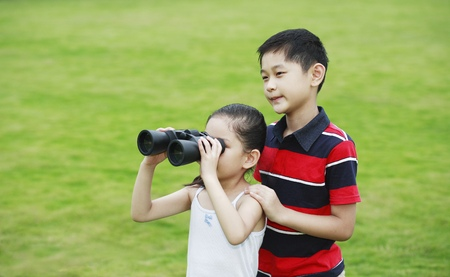 he   my sister: Brother and sister playing with binoculars in the park