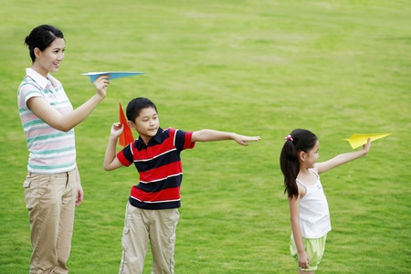 he   my sister: Mother and children playing with paper planes in the park