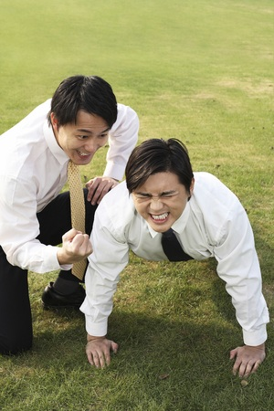 pushup: Businessman doing push-up with his colleague encouraging him LANG_EVOIMAGES