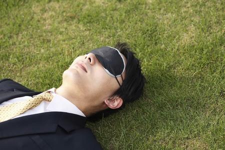 De negocios que duerme en el campo con máscara para los ojos que cubre sus ojos