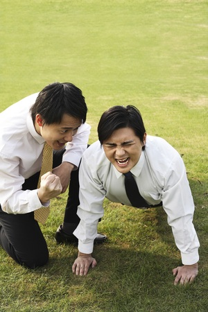 encouraging: Businessman doing push-up with his colleague encouraging him LANG_EVOIMAGES