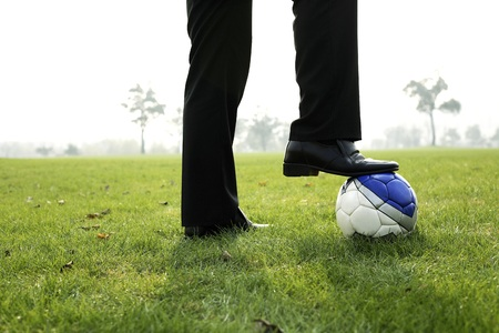 stepping on: Businessman stepping on a football